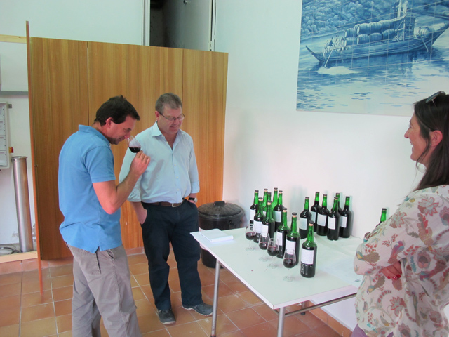 Charles and Henry discuss some of the freshly made Ports in the winery as Charles's wife, Marta, looks on.